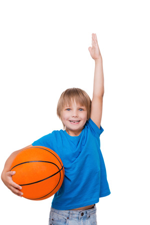 measure height: I want to be as tall! Cheerful little boy holding basketball ball and gesturing while standing isolated on white