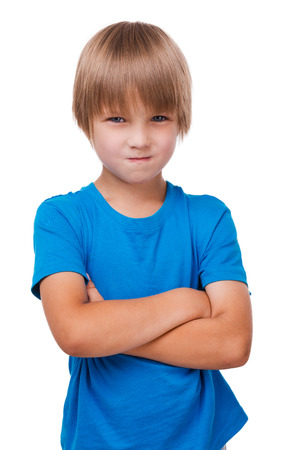 naughty boy: Naughty little boy. Sad little boy keeping arms crossed while standing isolated on white Stock Photo