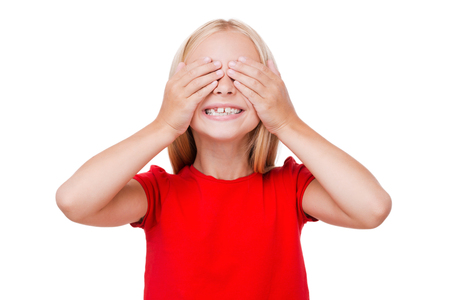 cute little girl smiling: I can see nothing! Cute little girl covering eyes with hands and smiling while standing isolated on white Stock Photo