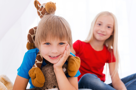 Having fun together. Two cute children having fun while sitting together on bed photo