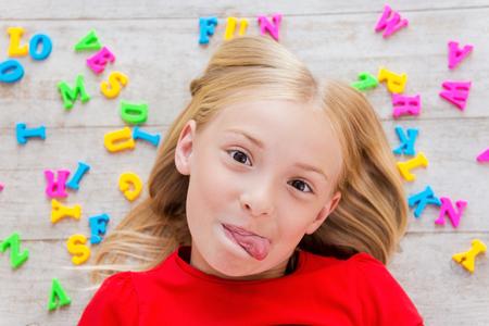 sacar la lengua: Cheeky niña. Vista superior de la niña linda que hace muecas mientras está acostado en el suelo con letras de colores de plástico que pone alrededor de su Foto de archivo