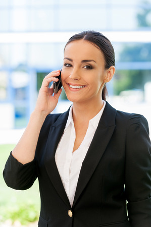 staying: Staying connected. Beautiful young woman in formalwear talking on the mobile phone and smiling while standing outdoors Stock Photo