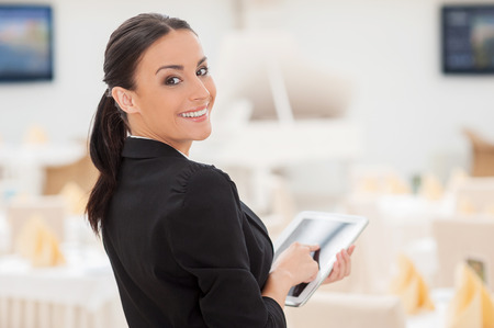 looking over shoulder: How may I help you? Attractive young woman in formalwear working on digital tablet and looking over shoulder while standing in restaurant