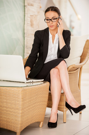 Busy working. Confident young woman in formalwear working on laptop and talking on the mobile phone while sitting at the comfortable chair Archivio Fotografico