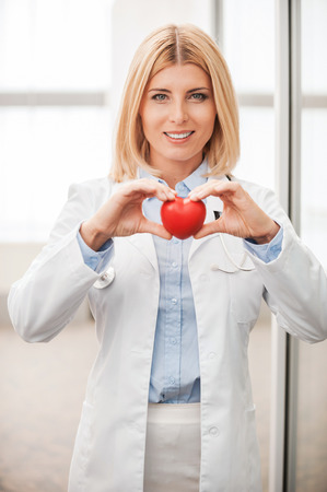 heart doctor: Confident female doctor in white uniform holding heart prop and smiling