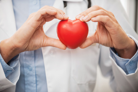 work heart: Taking good care of your heart. Close-up of female doctor in white uniform holding heart prop Stock Photo