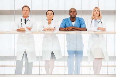 banister: Low angle view of four confident doctors standing close to each other and looking away while leaning at the handrail