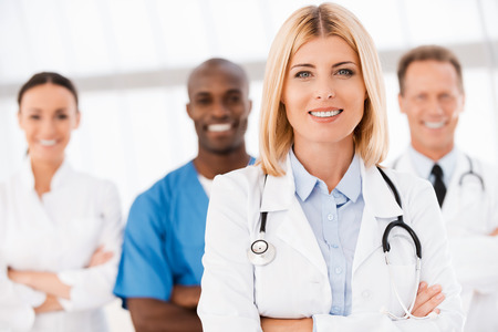 doctor female: Beautiful female doctor keeping arms crossed and smiling while her colleagues standing behind her in the background