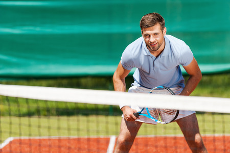 polo player: Confident tennis player. Handsome young man in polo shirt holding tennis racket and smiling while standing on tennis court Stock Photo