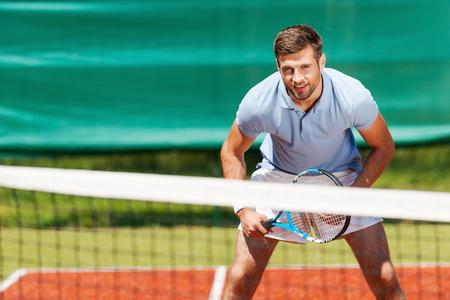jugando tenis: Tenista Confiado. Apuesto joven en camisa de polo sosteniendo la raqueta de tenis y sonriendo mientras está de pie en la cancha de tenis Foto de archivo