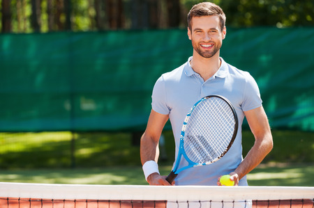 raqueta de tenis: Gran d�a para jugar! Hombre joven alegre en camisa de polo sosteniendo la raqueta de tenis y pelota mientras est� de pie en la pista de tenis