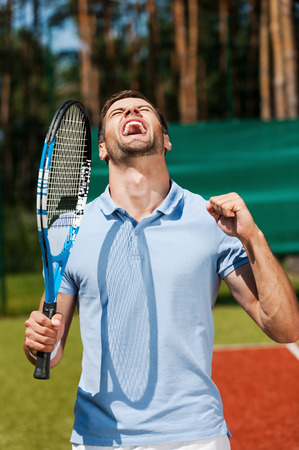 I am the best! Happy young man in polo shirt holding tennis racket and gesturing while standing on tennis court  photo