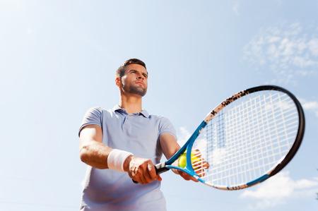 raqueta de tenis: Listo para servir. �ngulo de visi�n baja del hombre joven y guapo con camisa de polo sosteniendo la raqueta de tenis y pelota mientras est� de pie contra el cielo azul