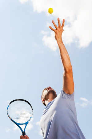 Serving a ball. Low angle view of tennis player serving a ball while standing against blue sky