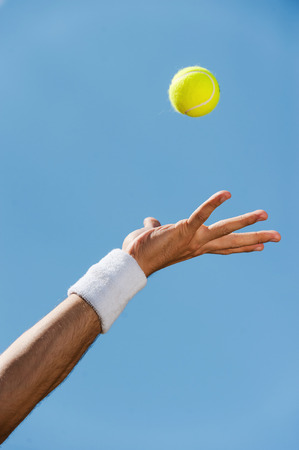 tennis ball: Serving ball. Close-up of male hand in wristband throwing tennis ball against blue sky