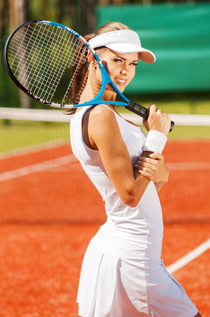 Are you ready to play?  Side view of beautiful young woman in sports clothing holding tennis racket and smiling photo