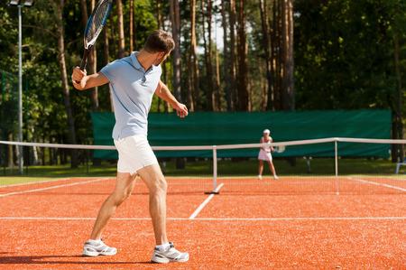 raqueta de tenis: Practicar con el amigo. Longitud total de hombre y mujer que juegan al tenis en la pista de tenis Foto de archivo