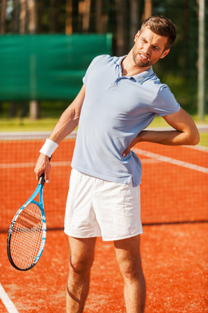 outdoor pursuit: Feeling pain in his back. Close-up of tennis player touching his back and grimacing while standing on the tennis court