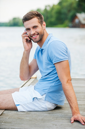 Handsome man on the phone. Side view of handsome young man talking on the mobile phone and smiling while sitting at the riverbank  photo