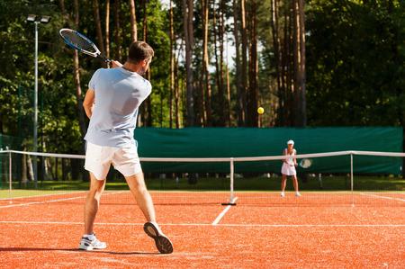 raqueta de tenis: Match point. Longitud total de hombre y mujer que juegan al tenis en la pista de tenis Foto de archivo