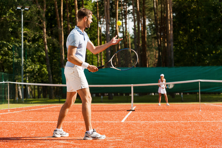 jugando tenis: Preparación para su mejor servicio. Longitud total de hombre y mujer que juegan al tenis en la pista de tenis Foto de archivo