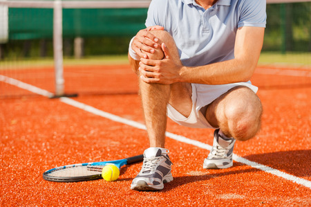 sports clothing: Sports injury. Close-up of tennis player touching his knee while sitting on the tennis court