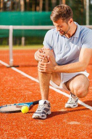 Feeling pain in knee. Close-up of tennis player touching his knee and grimacing while sitting on the tennis court photo
