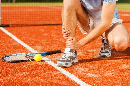 raqueta de tenis: Prevenci�n de lesiones deportivas. Primer plano de tenista tocar su pierna mientras est� sentado en la cancha de tenis Foto de archivo