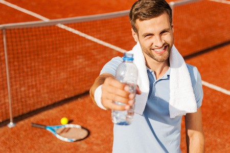 quench: Quench your thirst! Happy young man in polo shirt and towel on shoulders stretching out bottle with water while standing on tennis court  Stock Photo