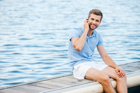 Staying connected everywhere. Handsome young man in polo shirt talking on the mobile phone and smiling while sitting on quayside  Stock Photo