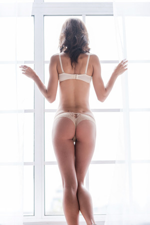 Curious beauty. Rear view of beautiful young woman in lingerie looking through the window   photo