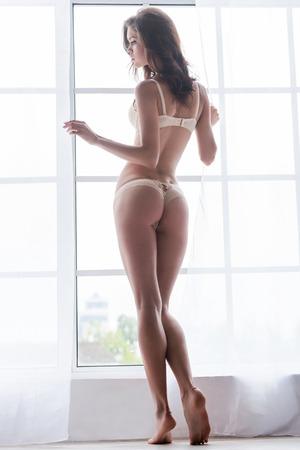 nalga: Confiados en su cuerpo perfecto. Vista posterior de cuerpo entero de la hermosa mujer joven en ropa interior de pie cerca de la ventana Foto de archivo