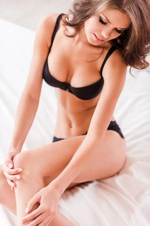 sexe de femme: Moments sensuels. Vue de dessus de la belle jeune femme brune de cheveux en lingerie noir assis dans son lit et de toucher sa jambe