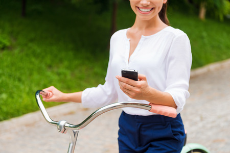 good news: Good news from friends. Close-up of young woman holding mobile phone and smiling while walking with her bicycle in park