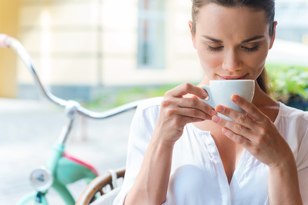 Coffee time. Attractive young woman drinking coffee and keeping eyes closed while sitting at the sidewalk cafe  photo