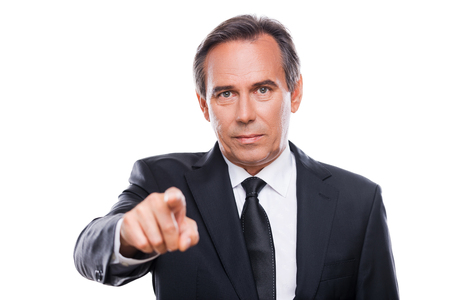 Businessman choosing you. Portrait of confident mature man in formalwear looking at camera and pointing you while standing against white background photo