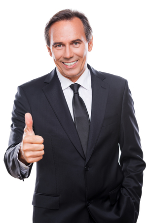 Good job! Confident mature man in formalwear looking at camera and smiling while showing his thumb up and standing against white background photo