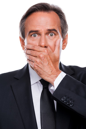 Surprised businessman. Surprised mature man in formalwear covering mouth with hand and looking at camera while standing isolated on white background photo