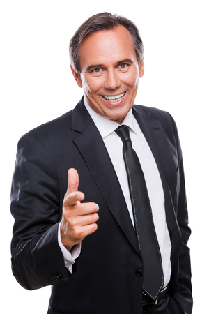 I choose you! Confident mature man in formalwear looking at camera and pointing you with smile while standing against white background photo