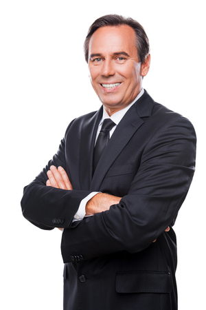 Confident and successful businessman. Waist up of confident mature man in formalwear looking at camera and smiling while keeping arms crossed and standing against white background Stock Photo