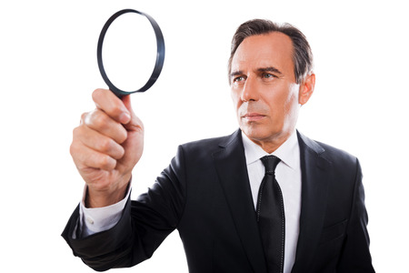 Businessman with magnifying glass. Concentrated mature man in formalwear looking through a magnifying glass while standing isolated on white background  photo