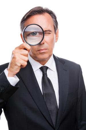 Businessman examining you. Serious mature man in formalwear examining you with magnifying glass while standing isolated on white background  photo