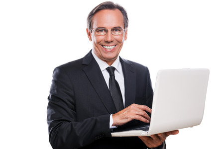 Supporting your business. Confident mature man in formalwear working on laptop and smiling while standing isolated on white background photo