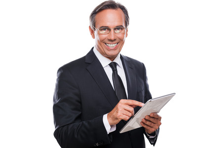 Businessman with digital tablet. Confident mature man in formalwear working on digital tablet and smiling while standing isolated on white background