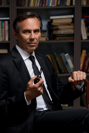 cane collar: Confident gentleman. Confident mature man in formalwear holding pipe and cane while sitting against bookshelf