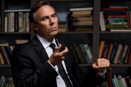 cane collar: Thoughtful gentleman. Confident mature man in formalwear holding pipe and cane while sitting against bookshelf Stock Photo