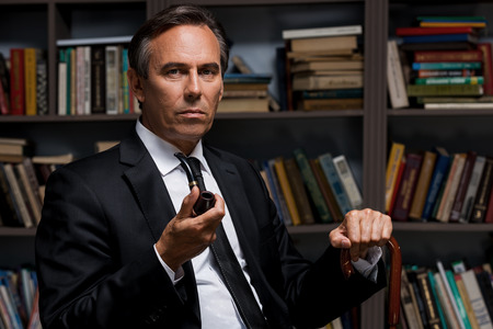 cane collar: Feeling confident and peaceful. Confident mature man in formalwear holding pipe and looking at camera while sitting against bookshelf