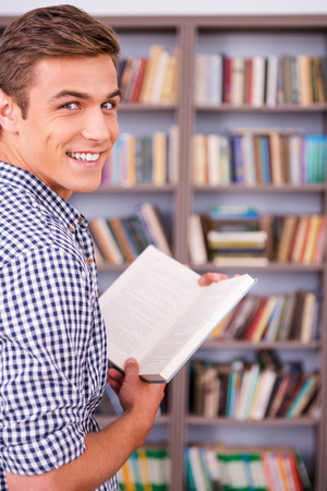 over the shoulder view: Happy bookworm. Rear view of happy young man holding book and looking over shoulder while standing against bookshelf