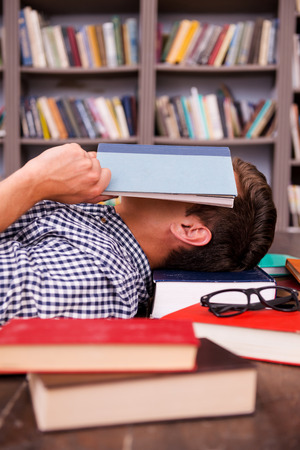 floor covering: Tired student. Side view of young man covering his face with book while lying on the hardwood floor with other books laying all around him  Stock Photo