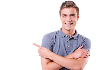 only adult: Look at this! Handsome young man pointing away and smiling while standing isolated on white background